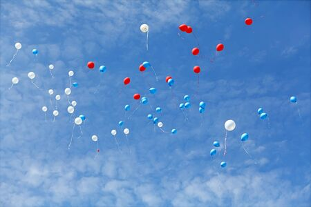 Rubber balloons flying in blue sky