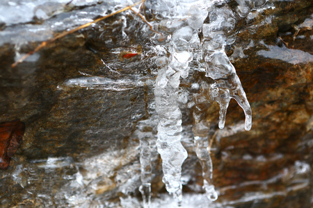 The thawing icicles with the falling water drop in the mountains of France in Vaujany in the winter Stock Photo