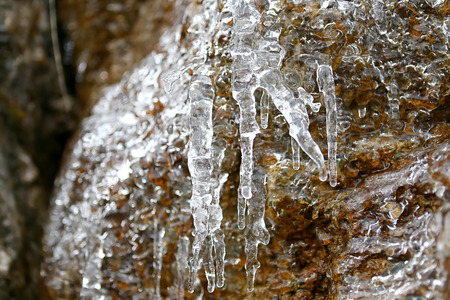 Icicles on a stone wall in the mountains of France in the winter