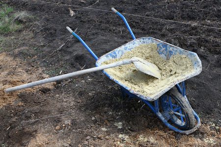 Construction tools - a shovel and the cart on wheels with sand on building of the house Standard-Bild - 104217514