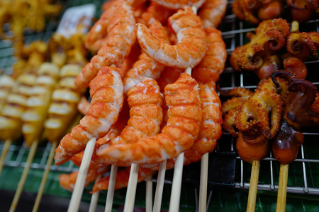 Seafood - fried fish in shrimp form and grilled octopus on market in Thailand
