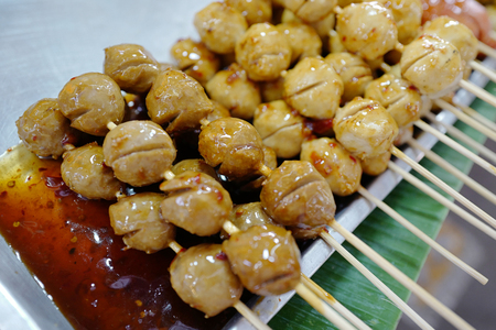 Grilled meat balls with spicy sause on Thai market Stock Photo