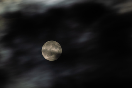 The moon circled by ghostly clouds moved by a strong wind