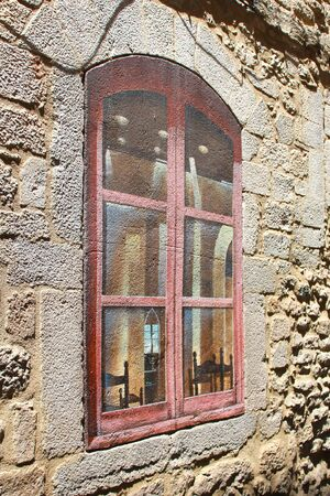 glance: On the lithoidal wall of ancient building a window is drawn. Time stopped. It is desirable to glance inward. But only wall before eyes. Stock Photo