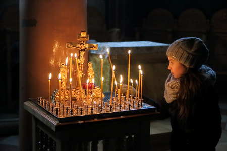 within: The picture was taken in a Christian church in the city of Chernivtsi in Ukraine. The picture shows the girl set the candle in a special candle before the image of the crucified Christ.