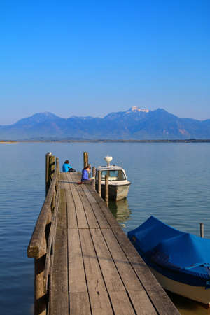 gentle dream vacation: The picture was taken in Germany, at Lake Chiemsee. The picture shows the pier for pleasure boats. On which sit a few people enjoying the beauty of the mountains in the evening light. One of the girls is reading a book.