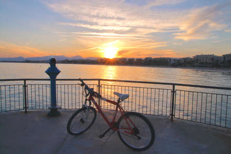 The picture was taken in Spain, on the edge of the marina in the town of Salou. In the photo seen a bicycle on the viewing platform. In the distance can be seen the sunset sea and mountains. Stock fotó