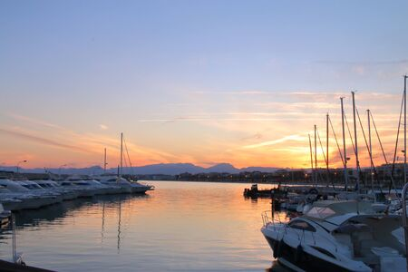 The picture was taken in Spain, Salou. The picture shows the sun setting over the marina located in the city harbor.