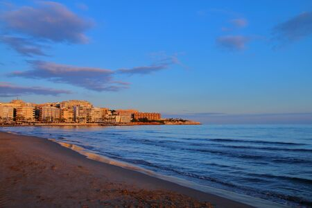 locality: The picture was taken in Spain, Salou. In the photo is visible the evening beach. In the background can be seen the city hotels in the rays of the setting sun. Stock Photo