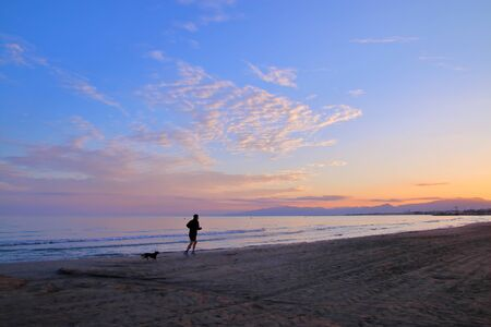 The picture was taken in Spain, on the beach in Salou. The picture shows a young man who commits an evening jog along the seas edge. Next to him running his friend - the dog.