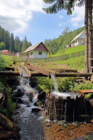The picture was taken in Ukraine, in the Carpathian Mountains. The picture shows the original village vat for washing. The vat is filled with water from a mountain stream in a natural way. Stock Photo