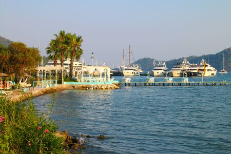 Photo taken in Turkey, in Gocek. In the photo there is a cafe located on the seashore and pier. On the background of the cafe you can see the marina with yachts. Banco de Imagens