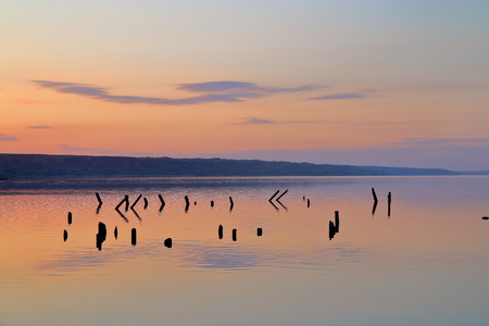 The picture was taken in Ukraine near the city of Odessa. In the photo there is a sunset over the smooth surface of the salt firth. The remains of a wooden pier are visible in the water.