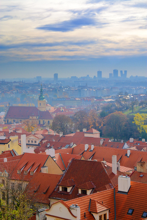 The photo was taken in Prague from the height of Prague Castle. The picture shows a view of the tiled roofs under a cloudy sky.