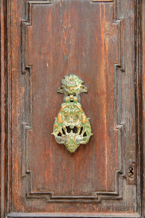 The photo was taken on the island of Malta in the ancient city of Mdina. The picture shows a vintage door knocker or a hammer. It is made of copper and turned green from a long time. 免版税图像
