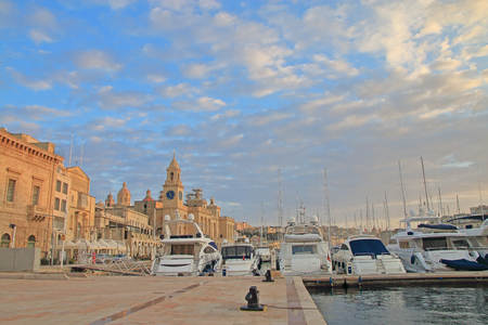 The photo was taken on the island of Malta in the city of Birgu. The picture shows yachts moored on the coast of the city in the evening against the backdrop of ancient architecture.