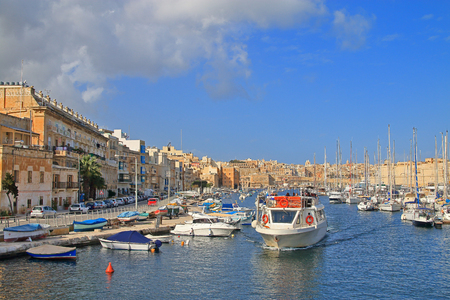 The photo was taken in the month of January in Malta. The picture shows a boat cruising the island's harbor along moored yachts and boats.