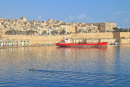 Photo taken on the island of Malta. The picture shows the morning in the bay of Valletta. The yellow architecture of the city is reflected from the sea surface.