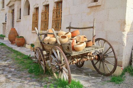 The photo was taken in Turkey, in the city of Uchisar. The picture shows an old cart loaded with ceramic dishes. 写真素材 - 132065216
