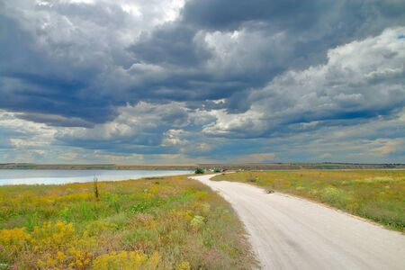The photo was taken in Ukraine near Odessa. Pictured is a steppe road along the estuary to a tourist camp. The landscape is captured under a picturesque sky.
