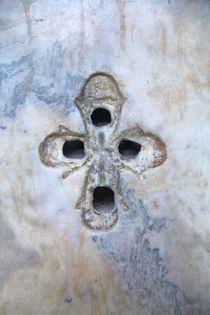 Photo taken in Turkey. The picture shows an ancient Christian cross with four holes in the marble wall inside the Hagia Sophia in Istanbul.