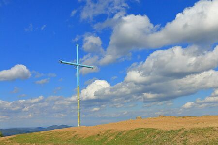 The photo was taken in Ukraine, in the Carpathian mountains. The picture shows a cross against the sky, mounted on top of a mountain called Makowice. Reklamní fotografie