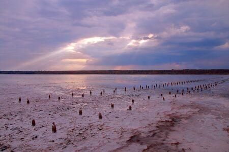 Das Foto wurde in der Ukraine in der Nähe der Stadt Odessa aufgenommen. Das Bild zeigt eine Landschaft einer salzigen Flussmündung namens Hadzhibeyevsky. Ein Sonnenstrahl durchdrang die Wolken und beleuchtete bei Sonnenuntergang die Wasseroberfläche.