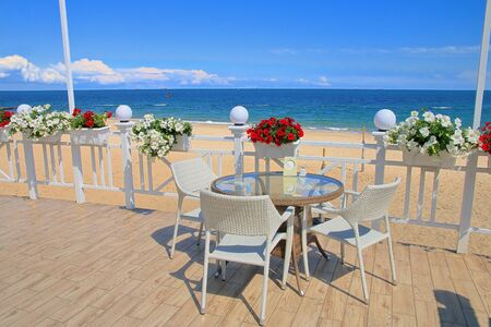 Photo taken on the Odessa coast. The picture shows a cozy veranda for relaxing on which stands a table and chairs. The veranda is decorated with pots of blooming flowers.