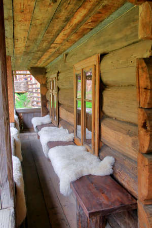 The photo was taken in the Ukrainian part of the Carpathian Mountains. In the picture there is a bench with skins of sheep in front of the entrance to the traditional rural dwelling of local residents - Gutsulov.