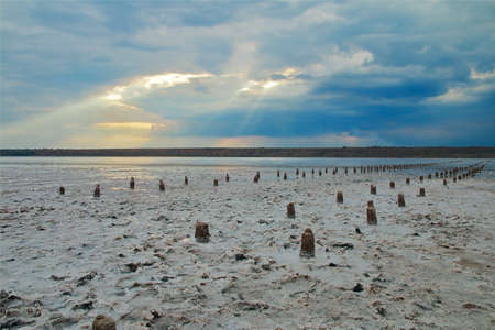 The photo was taken in Ukraine, near the city of Odessa. The picture shows a landscape of a salty estuary called Kuyalnik. A ray of sunshine pierced through the clouds, illuminating the surface of the water at sunset. Standard-Bild