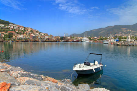 Photo taken in Turkey. The photo shows the landscape of the quay of the city of Alanya with a lonely white boat in the foreground.