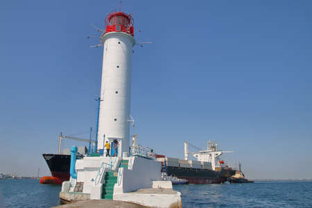 The photo was taken in the Odessa port. In the picture, a modern container ship sails near the old lighthouse. Guiding tugs are visible near the ship. 免版税图像