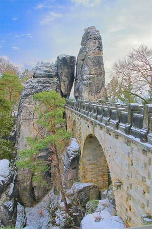 The photo was taken in Germany, in the mountains of Saxony. The picture shows a picturesque stone bridge called the Bastei.