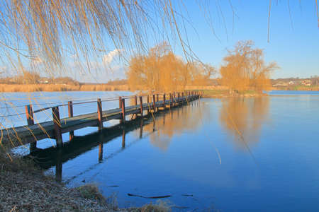 The picture was taken in Ukraine. The photo shows an old bridge to an island in the middle of a lake on an autumn day. 免版税图像