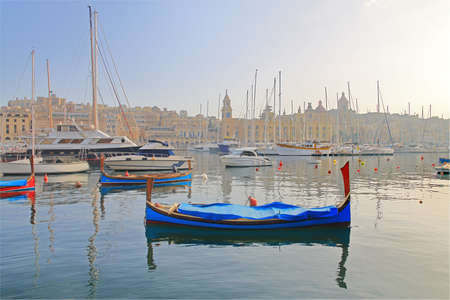 The photo was taken in Malta in the month of January. The picture shows the traditional boats painted in bright colors moored in the harbor of the island.