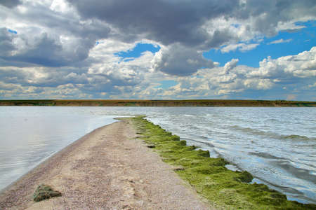 The photo was taken in Ukraine on an estuary called Tyligulskyi. The picture shows a narrow sand spit going into the estuary on a cloudy day. 免版税图像