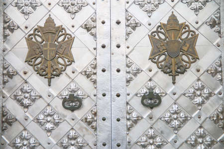 The picture was taken in the old town Kamenetz-Podolsk in Ukraine. The picture shows a stylish metal door of the temple. On the door hung the ancient coat of arms. 免版税图像