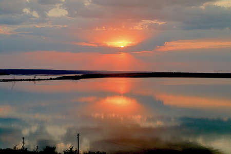The photo was taken in Ukraine near the city of Odessa. The picture shows a sunset over a calm estuary reflecting the evening sky. 免版税图像