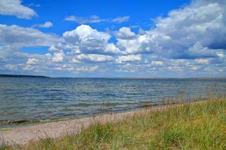 The photo was taken in Ukraine, in the area of the estuary called Tyligulskyi. The picture shows a summer landscape with a steppe, estuary, kitesurfing and a beautiful sky.