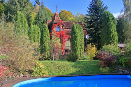 The photo was taken in Ukraine, in the Carpathian mountains. In the picture there is a house overgrown with wild grapes, in front of which is a garden and a pool.
