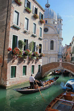 The photo was taken in the city of Venice. The picture shows a gondola sailing along the picturesque Canal.