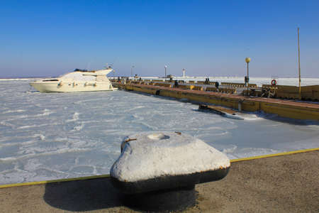 The photo was taken in the city of Odessa, in winter. The picture shows a bollard for mooring ships against the background of the frozen sea.