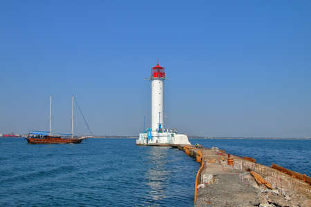 The photo was taken from the pier leading to the Odessa lighthouse. The picture shows a pleasure boat sailing near the white lighthouse.