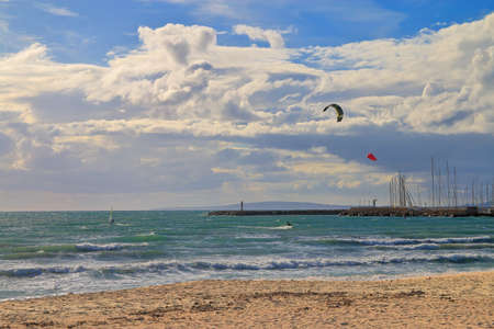 Photo taken in Spain on the island of Palma de Mallorca. The picture shows the coast of the island on an autumn windy day. In the distance, kitesurfers rolling along the sea waves are visible.