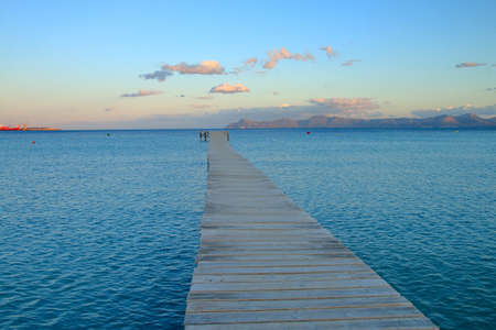 Photo taken on the island of Palma de Mallorca. The picture shows a wooden pier leaving for the sea photographed at sunset. 免版税图像
