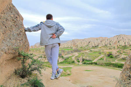 Photo taken in Turkey. The picture shows a young guy enjoying a beautiful view of the mountains of Cappadocia. 免版税图像