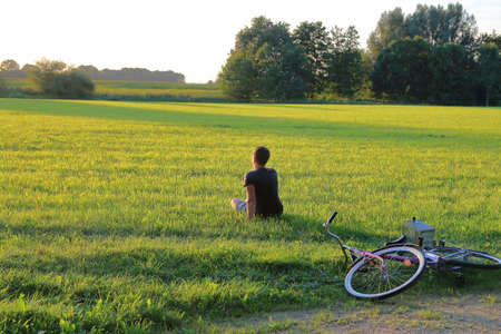 The picture shows a young dreamer sitting in a meadow and admiring the sunset. He is resting after a walk on the bike.