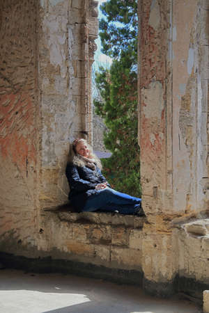 The photo shows a girl sitting on the windowsill of an old estate.