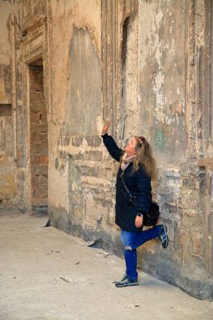 In the photo, the girl looks at the beautifully painted ceiling of an old estate.