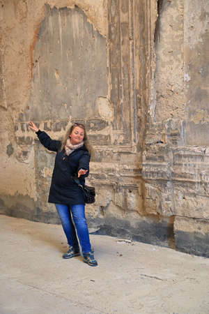 In the photo, a girl dancing against the background of the shabby wall of an old mansion called Kurisov.